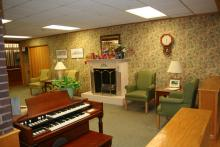 "Comfy ""den"" with fireplace, organ and chairs"
